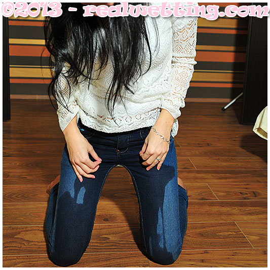 While lying on her tummy Antonia wets her jeans.