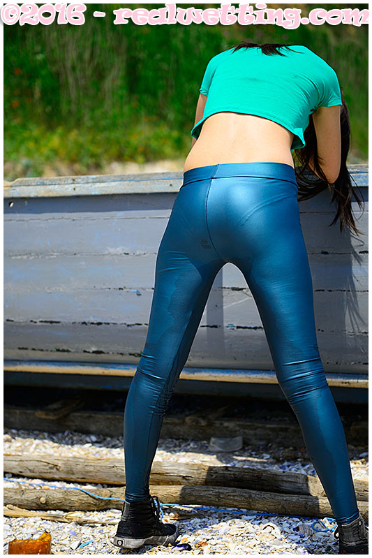 Debbie pees her blue shiny leggings on the beach wetting herself
