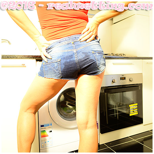 Bulging bladder pisses her jeans over the kitchen sink