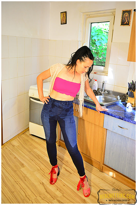 Wetting her jeans while doing the dishes