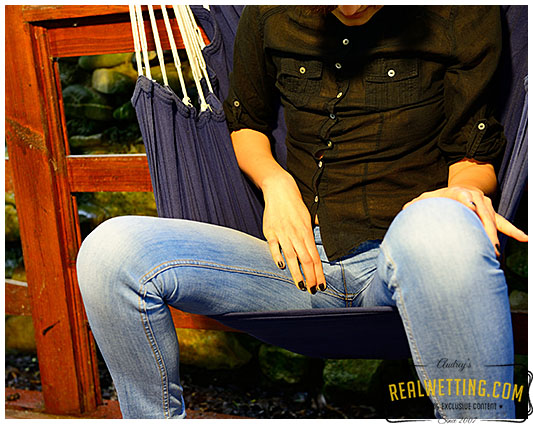 Sexy girl wetting her jeans sitting on hammock
